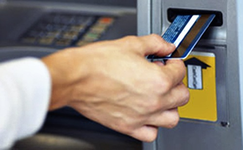 Close-up of man's hand inserting bank card into machine