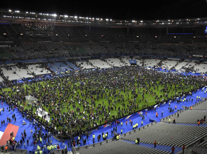 TOPSHOTS Spectators gather on the pitch of the Stade de France stadium following the friendly football match between France and Germany in Saint-Denis, north of Paris, on November 13, 2015, after a series of gun attacks occurred across Paris as well as explosions outside the national stadium where France was hosting Germany. At least 18 people were killed, with at least 15 people had been killed at the Bataclan concert hall in central Paris, only around 200 metres from the former offices of Charlie Hebdo which were attacked by jihadists in January.  AFP PHOTO / FRANCK FIFE